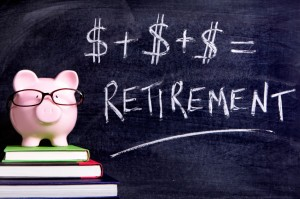 Picture of Pink piggy bank with glasses standing on books next to a blackboard with simple retirement formula. Sharp focus on the piggy bank.
