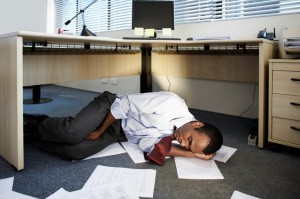 Picture of accountant sleeping under his desk.
