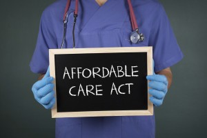 """Picture of doctor holding blackboard with words """"affordable care act."""""""
