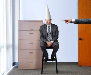 Business man wearing a dunce hat