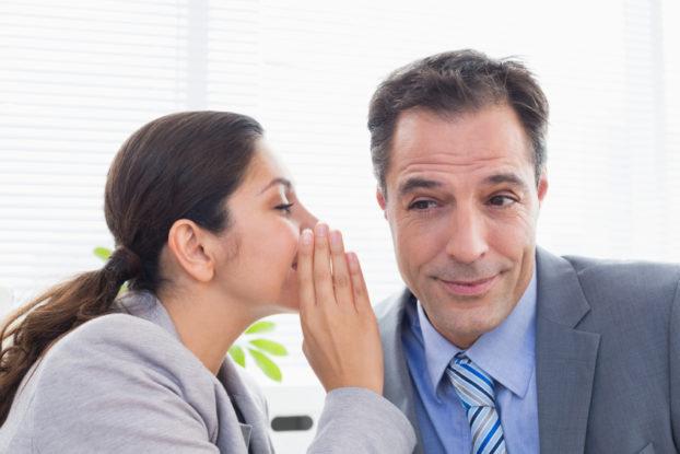 Picture of woman telling man a secret