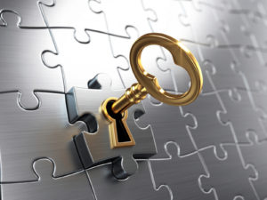Picture of a key unlocking ia puzzle piece