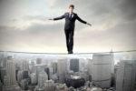 A man balances on a tight rope over a city skyline.