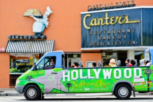 A picture of Los Angeles's Famous Canter's Deli Bakery and Restaurant, with a Hollywood sightseeing tour bus with tourists passing nearby.