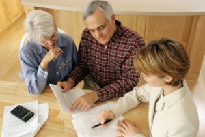 Picture of mature couple talking to financial planner at home.