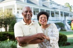 Picture of mature African American couple (50s and 60s) at a country club, standing in front of clubhouse. Main focus on woman.
