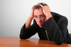 Picture of stressed out man holding head in his hands