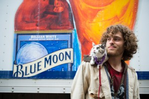 Picture of man standing in front of sign advertising Blue Moon brand beer