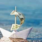 Picture of paper boat floating in water with dollar bill for sail.