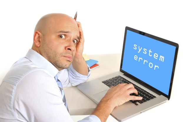 Picture of confused man sitting in front of computer that doesn't work.
