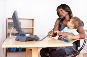 Picture of women working at computer with baby in lap
