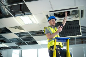Picture of construction worker doing something with HVAC system