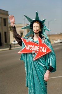 Picture of statute of liberty holding a sign that says income tax