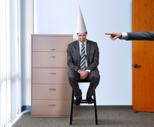 Business man wearing a dunce hat