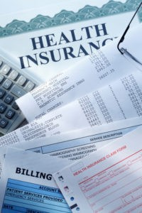 A health insurance claim form along with a couple of medical bills.