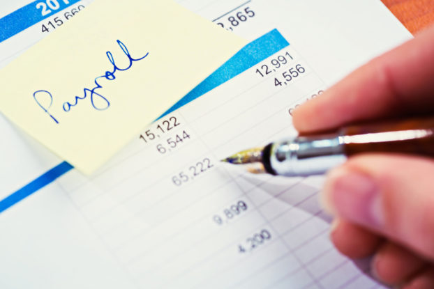 """A fountain pen checks a financial or business document with an adhesive note reading """"payroll"""" attached to it."""