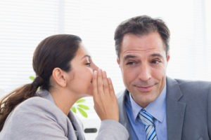 Picture of woman telling man a secret