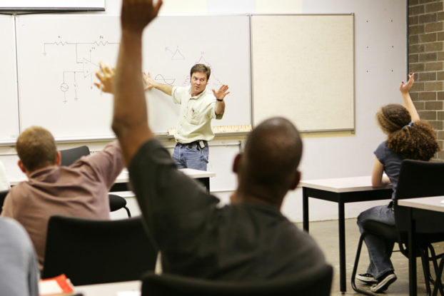 Picture of adult education class raising hands to ask questions.