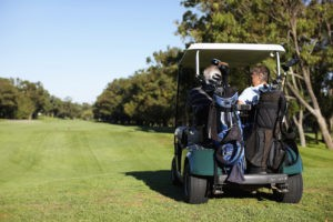 Picture of Golfing friends driving a golf car and going for a game of golf