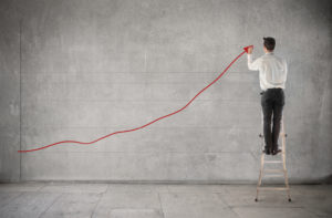 Picture of Businessman standing on a ladder and charting a graph with positive trend