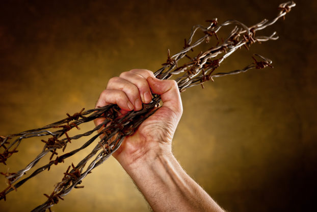 picture of man crushing a bundle of barbed wire