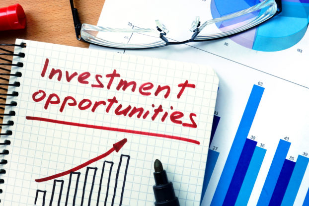picture of Notepad with investment opportunities on office wooden table.