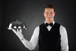 Portrait Of Happy Butler Holding Stainless Steel Cloche Over Tray