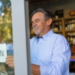 Picture of small business owner opening his wine shop