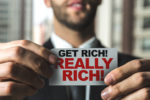 Picture for spotting investment scams post, which shows a man holding a get really rich sticker