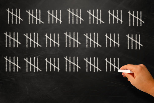 Picture of person counting real estate professional hours on a blackboard