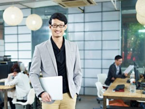 Picture of young asian entrepreneur standing in office with laptop computer under arm.