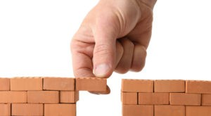 Picture of hand adding brick to a gap in the wall isolated on a white background