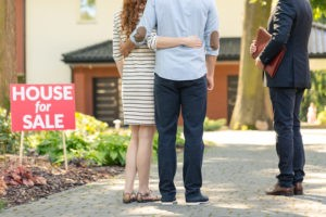 Couple standing with real estate agent selling them a home